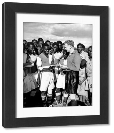 The English Footballer of the Year 1954, Tom Finney (r), shows one of his many international caps to the Northern Rhodesia Sportsman of the Year 1953, Inspector Wapamesa of the North Rhodesian Police (l), after giving a coaching exhibition in Lusaka