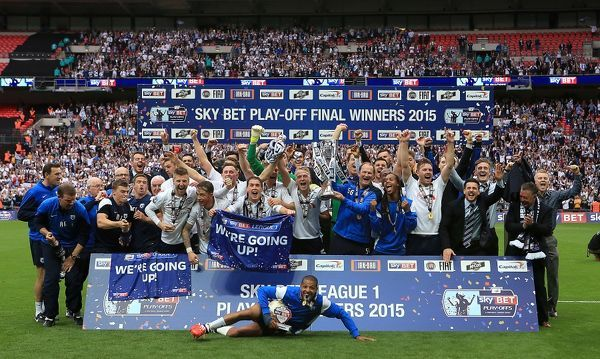 Preston North End lift the Sky Bet league One Play Off Final Trophy. On pitch celebrations, Jermaine Beckford slides in front of team mates with the match ball after his play-off final hat-trick