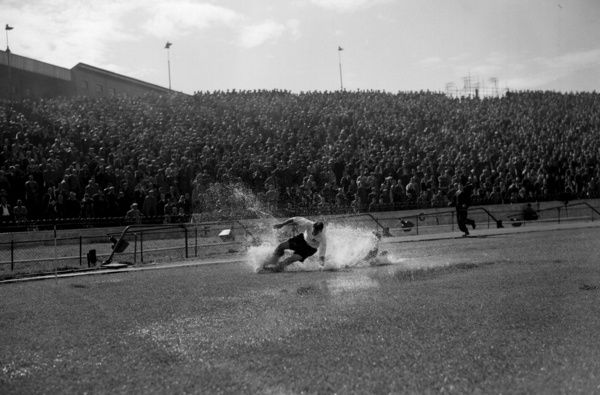PA NEWS PHOTO 25/8/56  TOM FINNEY ENGLAND AND PRESTON NORTH END FORWARD IN A SHOWER OF WATER SPRAY WHICH ALMOST COMPLETELY HIDES CHELSEA LEFT-BACK BELLET AS THEY TUSSLE FOR THE BALL ON THE SOAKED PITCH AT STAMFORD BRIDGE, LONDON